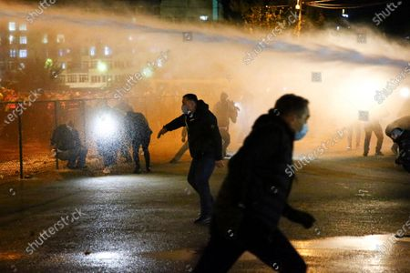Police use a water cannon toward demonstrators during a rally of supporters of the ex-President Mikhail Saakashvili's United National Movement, protesting the election results in Tbilisi, Georgia, on . Thousands of opposition supporters rallied Sunday in ex-Soviet Georgia to demand a snap vote after the opposition accused the ruling party of rigging tightly contested parliamentary elections