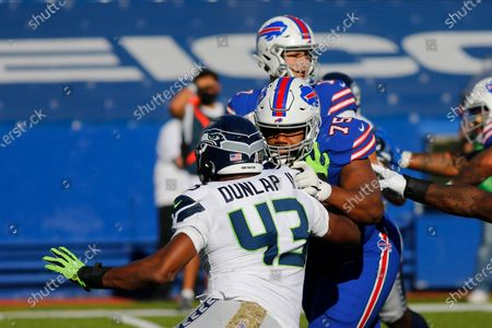 Buffalo Bills offensive tackle Daryl Williams (75) blocks Seattle Seahawks Carlos Dunlap (43) during the first half of an NFL football game, in Orchard Park, N.Y