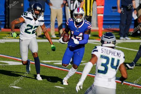 Buffalo Bills' Stefon Diggs (14) runs away from Seattle Seahawks' Quinton Dunbar (22) and Linden Stephens (34) during the first half of an NFL football game, in Orchard Park, N.Y