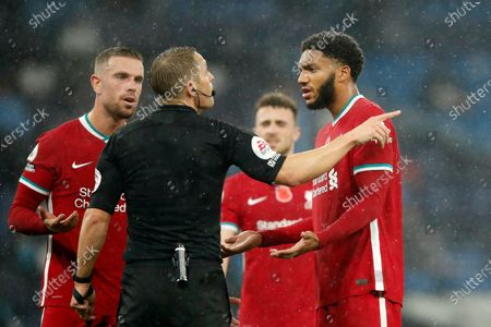 Referee Craig Pawson gestures to Liverpool's Joe Gomez, right, during the English Premier League soccer match between Manchester City and Liverpool at the Etihad stadium in Manchester, England
