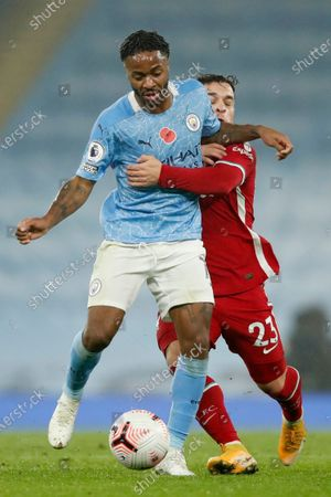 Liverpool's Xherdan Shaqiri fights for the ball with Manchester City's Raheem Sterling, left, during the English Premier League soccer match between Manchester City and Liverpool at the Etihad stadium in Manchester, England