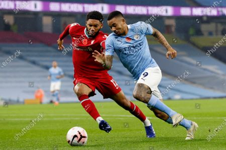 Liverpool's Joe Gomez vies for the ball with Manchester City's Gabriel Jesus, right, during the English Premier League soccer match between Manchester City and Liverpool at the Etihad stadium in Manchester, England