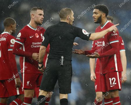 Liverpool players Jordan Henderson (L) and Joe Gomez (R) argue with referee Craig Pawson (C) during the English Premier League soccer match between Manchester City and Liverpool FC in Manchester, Britain, 08 November 2020.