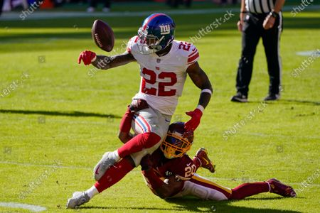 Washington Football Team cornerback Jimmy Moreland (20) breaks up a pass intended for New York Giants running back Wayne Gallman (22) in the first half of an NFL football game between the New York Giants and Washington Football Team, in Landover, Md