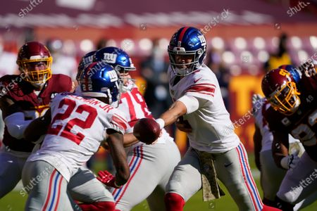 New York Giants quarterback Daniel Jones (8) hands the ball off to running back Wayne Gallman (22) during the first half of an NFL football game against the Washington Football Team, in Landover, Md
