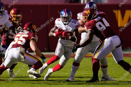 New York Giants running back Wayne Gallman (22) runs with the ball against Washington Football Team linebacker Cole Holcomb (55) and Washington Football Team defensive tackle Daron Payne (94) in the first half of an NFL football game, in Landover, Md