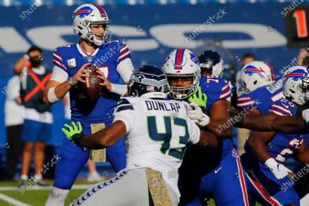 Buffalo Bills quarterback Josh Allen, left, looks to pass as teammate offensive tackle Daryl Williams (75) blocks Seattle Seahawks Carlos Dunlap (43) during the first half of an NFL football game, in Orchard Park, N.Y