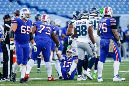 Buffalo Bills quarterback Josh Allen (17) is helped up by a teammate after being sacked by Seattle Seahawks' Carlos Dunlap during the second half of an NFL football game, in Orchard Park, N.Y