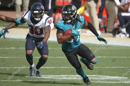 Jacksonville Jaguars' Chris Claybrooks runs with the ball pat Houston Texans' Cornell Armstrong (30) during the first half of an NFL football game, in Jacksonville, Fla