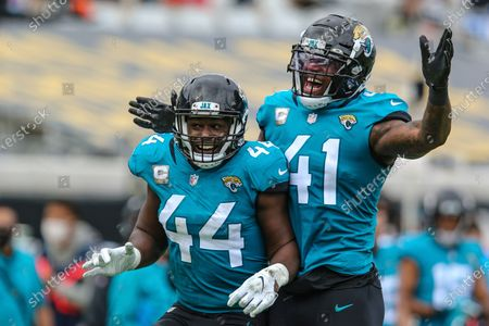 Jacksonville Jaguars linebacker Josh Allen (41), riight, and linebacker Myles Jack (44) celebrate a fumble recovery during the first half of an NFL football game against the Houston Texans, in Jacksonville, Fla