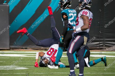 Houston Texans wide receiver Randall Cobb (18) is tackled by Jacksonville Jaguars free safety Jarrod Wilson (26) during the first half of an NFL football game, in Jacksonville, Fla