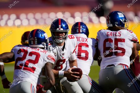 New York Giants quarterback Daniel Jones (8) prepares to hands the ball to running back Wayne Gallman (22) in the first half of an NFL football game between the New York Giants and Washington Football Team, in Landover, Md