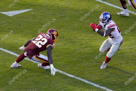 New York Giants running back Wayne Gallman (22) goes up against Washington Football Team safety Deshazor Everett (22) in the first half of an NFL football game, in Landover, Md