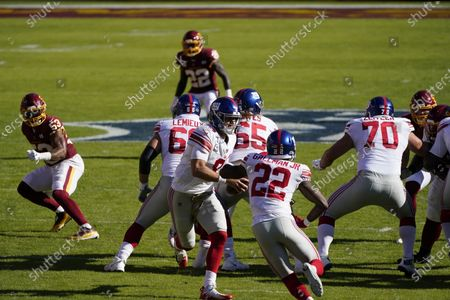 New York Giants quarterback Daniel Jones (8) hands the ball to running back Wayne Gallman (22) in the first half of an NFL football game between the New York Giants and Washington Football Team, in Landover, Md