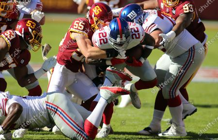 New York Giants running back Wayne Gallman (22) in action against Washington Football Team linebacker Cole Holcomb (55) during an NFL football game against the New York Giants, in Landover, Md