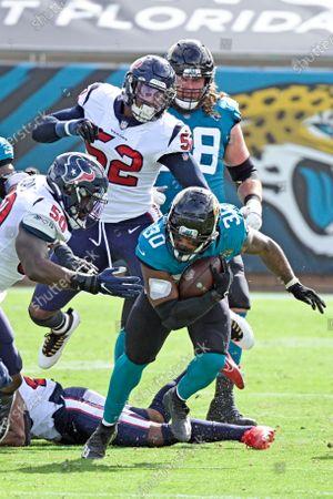 Jacksonville Jaguars running back James Robinson (30) runs for yardage against Houston Texans linebacker Tyrell Adams (50) and linebacker Jonathan Greenard (52) during the first half of an NFL football game, in Jacksonville, Fla