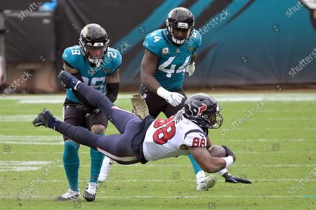 Houston Texans tight end Jordan Akins (88) is tackled by Jacksonville Jaguars safety Josh Jones (29) and linebacker Myles Jack (44) after a reception during the first half of an NFL football game, in Jacksonville, Fla