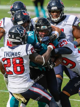Stock Photo of Jacksonville, FL, U.S: Jacksonville Jaguars running back Chris Thompson (34) is tackled by a host of Texans defenders during 1st half NFL football game between the Houston Texans and the Jacksonville Jaguars at TIAA Bank Field in Jacksonville, Fl