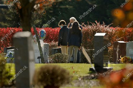 Wilmington, Pennsylvania-Nov. 8, 2020-President-elect Joe Biden, center, salutes his son Beau Biden's grave after, attending church at St. Joseph on the Brandywine Roman Catholic Church in Wilmington, Delaware on Nov.8, 2020. Accompanying Biden is his grandson Hunter Biden, left, son of Beau Biden, and his daughter-in-law Hallie Biden, (wife of Beau Biden). (Carolyn Cole / Los Angeles Times)
