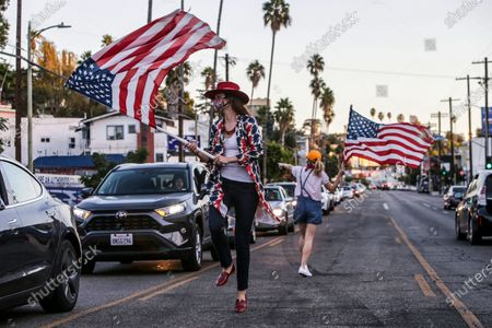 Los Angeles, CA, Saturday, November 7, 2020 - Katherine Fairfax Wright, left and Katy Wicker dance along the median on Sunset Blvd., celebrating the presidential election of Joe Biden. (Robert Gauthier/ Los Angeles Times)