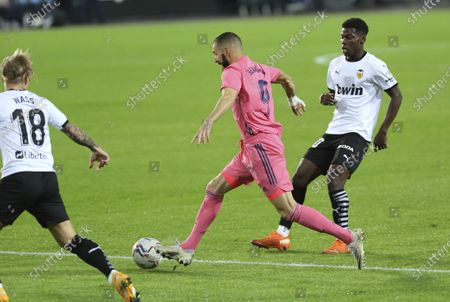 Real Madrid's Karim Benzema, center, controls the ball during the Spanish La Liga soccer match between Valencia and Real Madrid at the Mestalla Stadium in Valencia, Spain