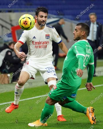 Lyon's Leo Dubois, left, challenges for the ball with Saint-Etienne's Miguel Angel Trauco Saavedra, right, during the French League One soccer match between Lyon and Saint-Etienne in Decines, near Lyon, central France