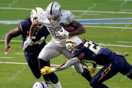 Las Vegas Raiders tight end Darren Waller, center, splits between Los Angeles Chargers defensive end Melvin Ingram, left, and strong safety Rayshawn Jenkins during the first half of an NFL football game, in Inglewood, Calif