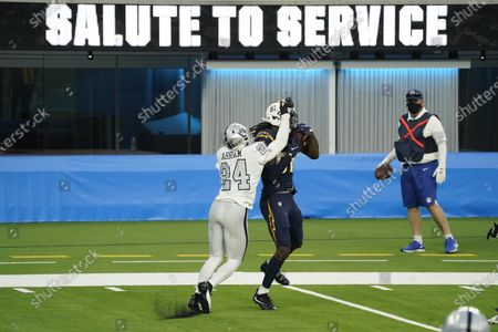 Stock Picture of Los Angeles Chargers wide receiver Mike Williams makes a catch and Las Vegas Raiders strong safety Johnathan Abram defends in front of Salute To Service signage during the second half of an NFL football game against the Las Vegas Raiders, in Inglewood, Calif