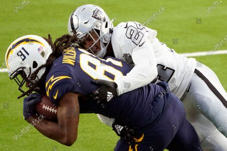 Los Angeles Chargers wide receiver Mike Williams, left, pulls down a catch was Las Vegas Raiders strong safety Johnathan Abram defends during the second half of an NFL football game, in Inglewood, Calif