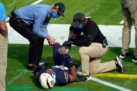 Los Angeles Chargers running back Justin Jackson works with trainers after an injury during the first half of an NFL football game against the Las Vegas Raiders, in Inglewood, Calif