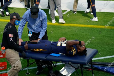 Stock Photo of Los Angeles Chargers running back Justin Jackson works with trainers after an injury during the first half of an NFL football game against the Las Vegas Raiders, in Inglewood, Calif
