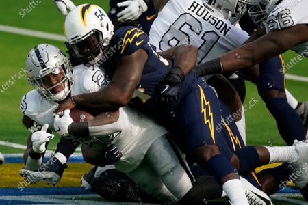 Las Vegas Raiders running back Josh Jacobs, left, is hauled down by Los Angeles Chargers defensive end Melvin Ingram during the first half of an NFL football game, in Inglewood, Calif