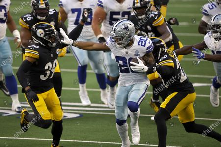 Stock Image of Dallas Cowboys running back Tony Pollard (20) fights for yards while Pittsburgh Steelers safety Minkah Fitzpatrick (39) and cornerback Steven Nelson (22) attempt a tackle during the first half of an NFL football game in Arlington, Texas