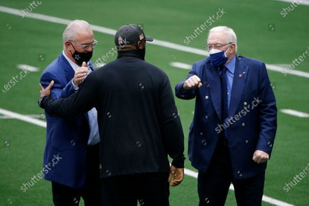 Dallas Cowboys chief operating officer/director of player personnel Stephen Jones, left, and owner Jerry Jones, right, greet Pittsburgh Steelers head coach Mike Tomlin, center, during team warmups before an NFL football game in Arlington, Texas