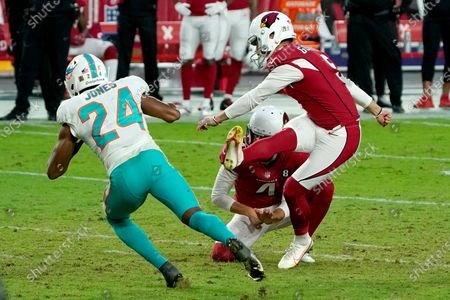 Arizona Cardinals kicker Zane Gonzalez unsuccessfully attempts a game-tying field goal as punter Andy Lee (4) holds during the second half of an NFL football game as Miami Dolphins cornerback Byron Jones (24) defends, in Glendale, Ariz. The Dolphins won 34-31