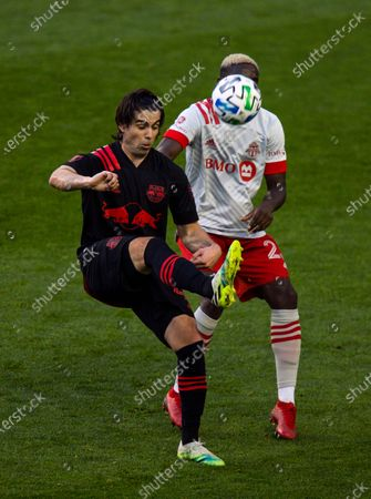 New York Red Bulls attacker Brian White, right, fights for the ball with Toronto FC defender Chris Mavinga during an MLS soccer match, in Harrison, N.J
