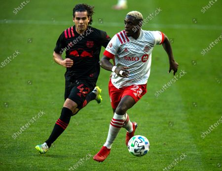 Toronto FC defender Chris Mavinga, right, fights for the ball against New York Red Bulls attacker Brian White during an MLS soccer match, in Harrison, NJ