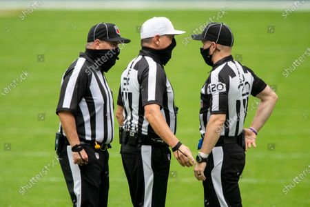 From left, NFL umpire Paul King (121), referee John Hussey (35) and side judge Jonah Monroe (120) wear masks and talk on the field as the Los Angeles Rams take on the Miami Dolphins during an NFL football game, in Miami Gardens, Fla
