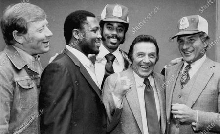 Comedian Norm Crosby, second from right, gives a thumbs-up as he is surrounded by sports figures, from left, Mickey Mantle, Joe Frazier, Walt Frazier and Nick Buoniconti in New York, to launch a new ad campaign for a light beer. Crosby, the deadpan mangler of the English language who thrived in the 1960s, '70s and '80s as a television, nightclub and casino comedian, has died. He was 93. Crosby's daughter-in-law, Maggie Crosby, told the New York Times that the comic died of heart failure in Los Angeles