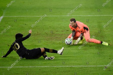 Portland Timbers goalkeeper Steve Clark, right, makes a save as Los Angeles FC midfielder Eduard Atuesta plays a pass during the second half of an MLS soccer match in Los Angeles, . The game ended in a 1-1 draw