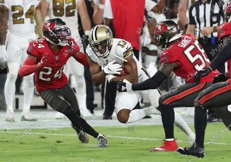 New Orleans Saints wide receiver Michael Thomas (13) is stopped by Tampa Bay Buccaneers cornerback Carlton Davis (24) and outside linebacker Shaquil Barrett (58) during the first half of an NFL football game, in Tampa, Fla