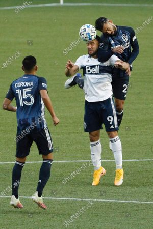 Vancouver Whitecaps forward Lucas Cavallini, center, heads the ball as Los Angeles Galaxy defender Giancarlo Gonzalez, right, defends and Los Angeles Galaxy midfielder Joe Corona, left, looks on during the first half of an MLS soccer match in Portland, Ore