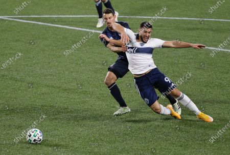 Stock Image of Los Angeles Galaxy defender Daniel Steres, left, defends against Vancouver Whitecaps forward Lucas Cavallini, right, during the first half of an MLS soccer match in Portland, Ore., . The Whitecaps defeated the Galaxy 3-0