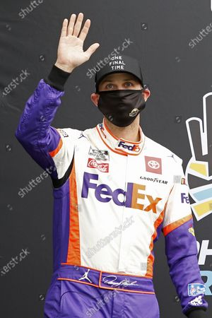 Denny Hamlin waves to the crowd during driver introductions prior to the NASCAR Cup Series auto race at Phoenix Raceway, in Avondale, Ariz