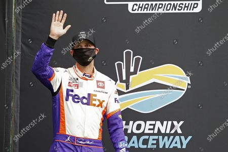 Stock Photo of Denny Hamlin waves to the crowd during driver introductions prior to the NASCAR Cup Series auto race at Phoenix Raceway, in Avondale, Ariz