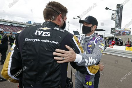 Jimmie Johnson, right, is greeted by opposing team members prior to a NASCAR Cup Series auto race at Phoenix Raceway, in Avondale, Ariz