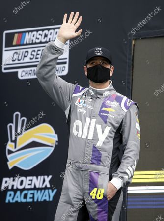 Jimmie Johnson waves to the crowd during driver introductions prior to the NASCAR Cup Series auto race at Phoenix Raceway, in Avondale, Ariz