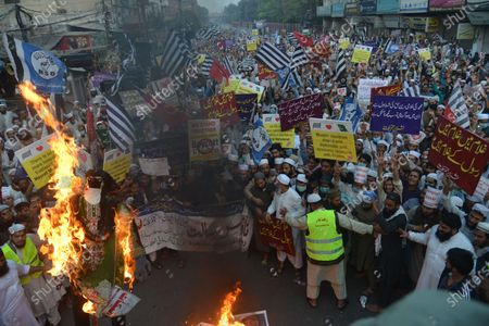 Pakistani supporters of the religious group Shabban Khatam-e-Nabuwat hold placards and burn the effigies of Asia Bibi (L), a Pakistani Christian woman who spent eight years on death row on blasphemy charges, and French President Emmanuel Macron (R) during protest demonstrating rally against the French President Emmanuel Macron and the republishing in France of caricatures of the Prophet Muhammad they deem blasphemous in Lahore.