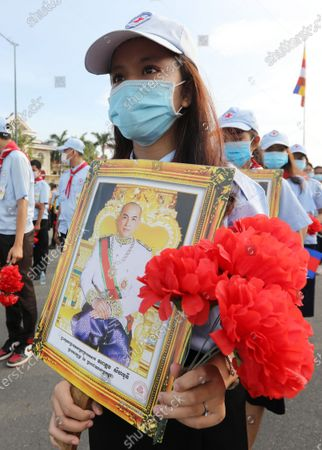 A student holds a portrait of King Norodom Sihamoni during a ceremony at the Independence Monument in Phnom Penh, Cambodia, 09 November 2?020. Cambodia marked its 67th anniversary of independence from France on 09 November 2020.