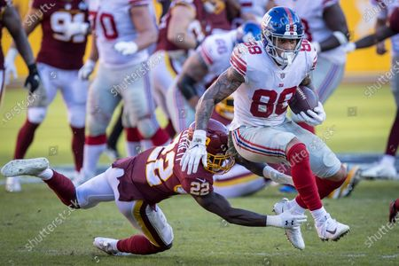 New York Giants tight end Evan Engram (88) jumps out of the tackle of Washington Football Team safety Deshazor Everett (22) during the NFL Game between the New York Giants and Washington Football Team at FedEx Field in Landover, Maryland Photographer: Cory Royster